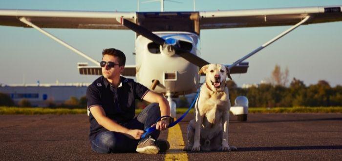 Joven con mascota en pista de aviones | Consejos para viajar en avión