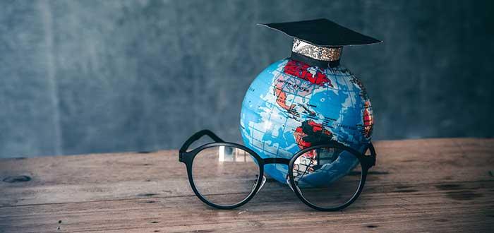 Mapamundi y espejuelos simbolizando estudiar en el extranjero