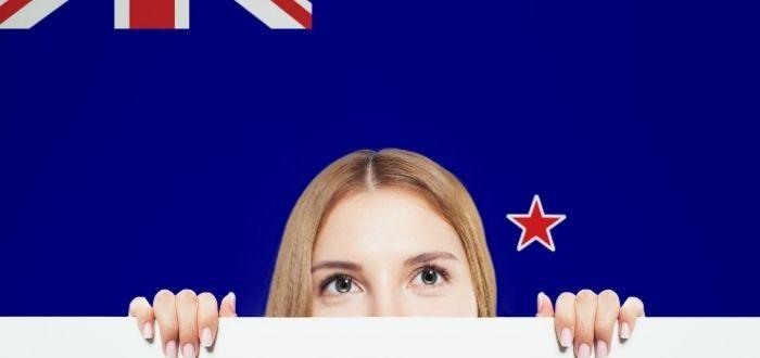 Estudiante con bandera de Nueva Zelanda al fondo