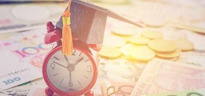Reloj y birrete de graduación sobre dinero en efectivo
