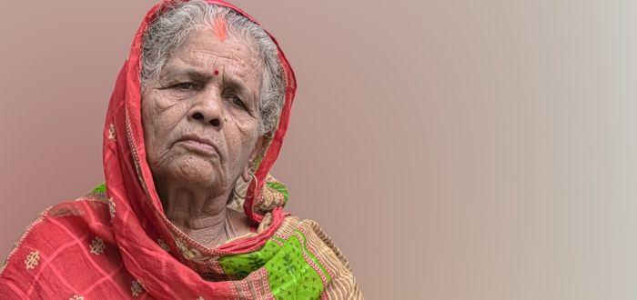 Mujer anciana usando bindi y sari